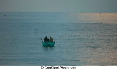Sea fishing - Two fishers in round fishing boat at the sea.