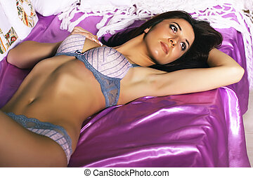 woman lying in bed - Beautiful young woman wearing lingerie...