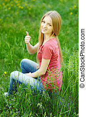 Smiling female sitting outdoors gesturing thumb up against...
