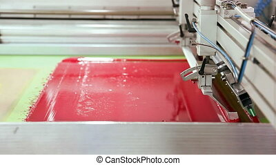 Screen printing machine working, printing magenta
