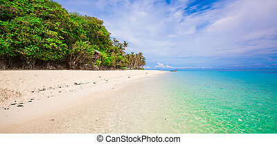 Panoramic view of white beach with turquoise water and blue sky