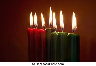 Kwanzaa Candles - Seven Kwanzaa candles with flames lit on...