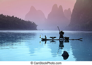 YANGSHUO - JUNE 18: Chinese man fishing with cormorants birds in Yangshuo, Guangxi region, traditional fishing use trained cormorants to fish, June 18, 2012 Yangshuo in Guangxi, China