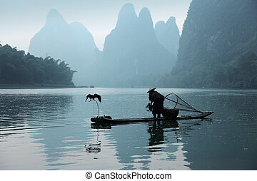 Chinese man fishing with cormorants birds, traditional...