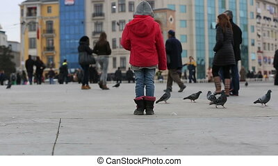 pedestrian walking on the Taksim Sq - red girl feeding flock...