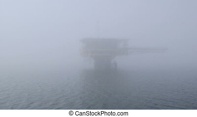 Automated gas production offshore platform in the misty sea...