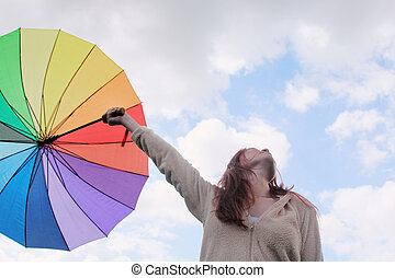 Woman with umbrella on the background of cloudly sky