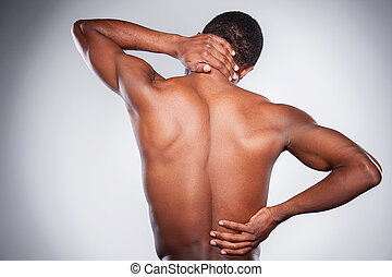 Pain in joint. Rear view of young shirtless African man...