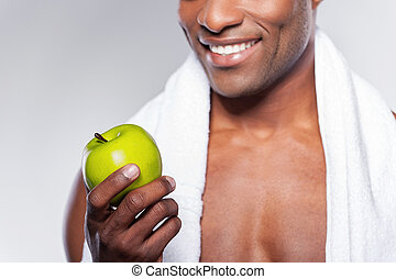 Man with green apple. Cropped image of young muscular...