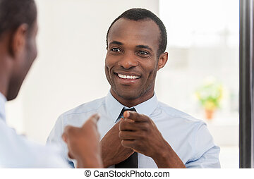 Feeling confident Young African man adjusting his necktie...