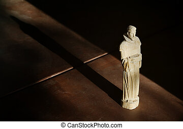 Wooden Statue of St Francis in Afternoon Light with Shadow