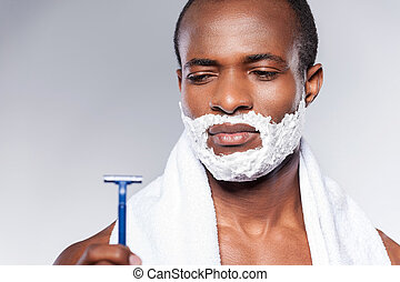 Really bad razor. Young shirtless African man looking at the...