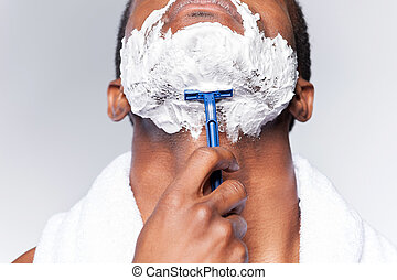 Close up of man shaving. Close up of young African man...