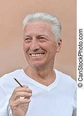 man smoking cigarette - Portrait of happy nice senior man...