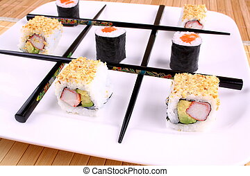 Tic tac toe play with chopsticks and sushi, close up