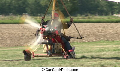 Motorized hang glider taking off from grass field