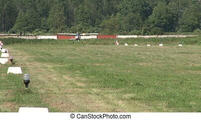 Light aircraft landing on grass field