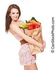 Health food. - Gorgeous young brunette woman holding big bag...