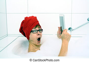 Delighted woman in bathtub with tablet computers, close up