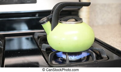 Turning off gas stove with tea kettle
