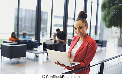 Beautiful young african woman with laptop in modern office -...