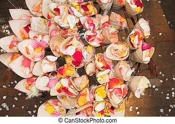 rose petal confetti - A flower and feather arrangement with...