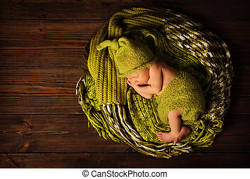 baby newborn portrait, kid sleeping in woolen hat on brown...