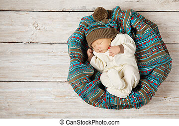 baby newborn sleeping in woolen hat on white wooden...