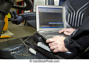 Mechatronic engine check - Laptop, hooked up to a forklift's...