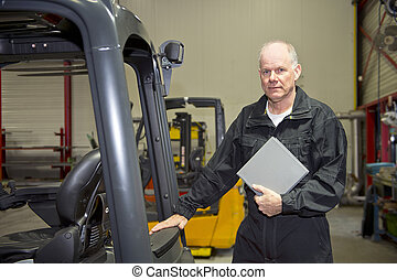 Maintenance engineer with manual - Forklift maintenance...