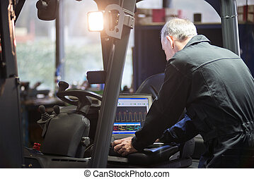 Electronic engine tuning - Mechanic using a laptop to...