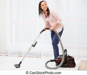 Young cheerful brunette woman vacuum cleaning carpet in home...