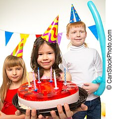 Happy little children celebrating birthday with cake