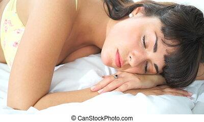 brunette sleeping in her bed - brunette woman sleeping in...