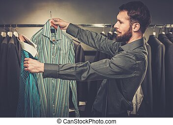 Handsome man with beard choosing shirt in a shop
