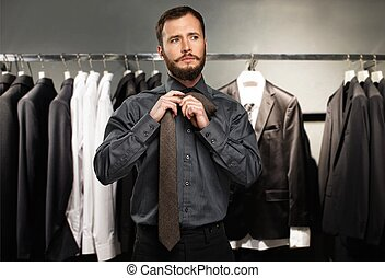 Handsome man with beard tying a tie in a clothing store