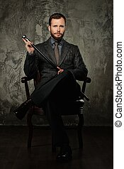 Handsome well-dressed with stick sitting in leather chair
