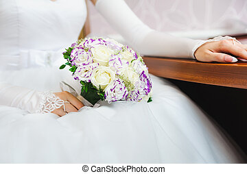bride in white dress holding bouquet of delicate roses