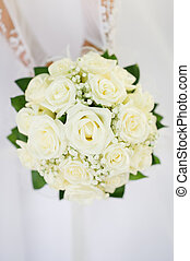 Wedding bouquet with many white roses in hands of bride