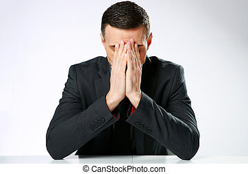Frustrated businessman sitting at the table with hands on...
