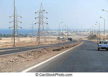 Suetsky channel, Egypt - Novenber 11, 2008: The road from Cairo to Hurghada. Cars driving on the road. Oil facilities away.