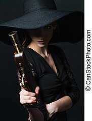girl pirate with ancient pistol in hand on a black...