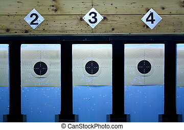 Three rifle targets in a shooting gallery