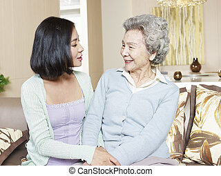 senior mother and adult daughter - senior asian mother...