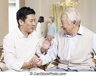senior father and adult son - senior asian father chatting...