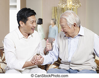 father and adult son - asian father and adult son chatting...