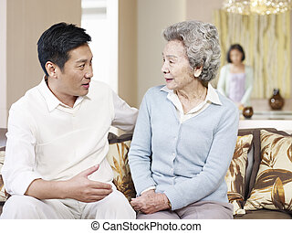 mother and adult son - asian mother and adult son chatting...