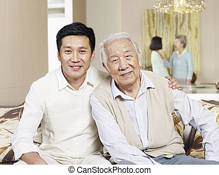 senior father and adult son - home portrait of asian father...