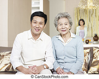 senior mother and adult son - home portrait of asian mother...