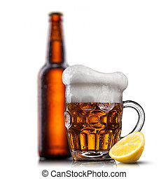 Beer in glass with water drops and lemon against bottle isolated on white